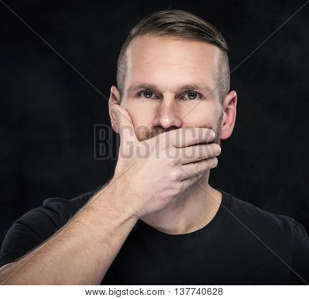 Man with hand covering his mouth on dark background.