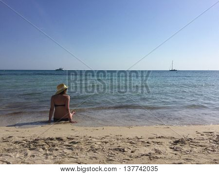 Bikini woman wearing a hat on the beach while sitting in the sea
