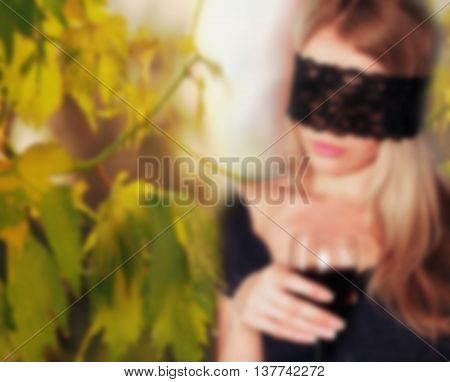 Sexy Young Blond Woman With Black Lace On Her Eyes Blindfolded, Holding A Glass Of Wine On The Backg