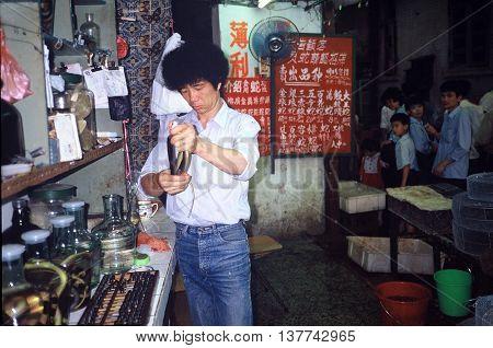 GUANGZHOU / CHINA - CIRCA 1987: A vendor holds a snake in Guangzhou's Qingping Market.