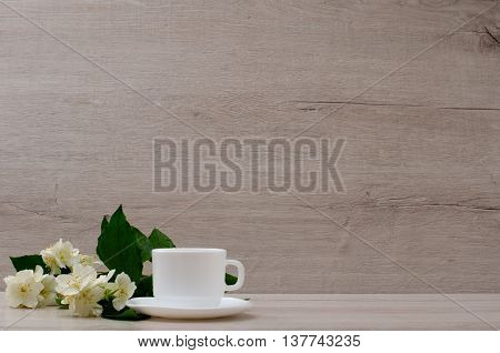 White mug and a branch of jasmine on the wood background space for text