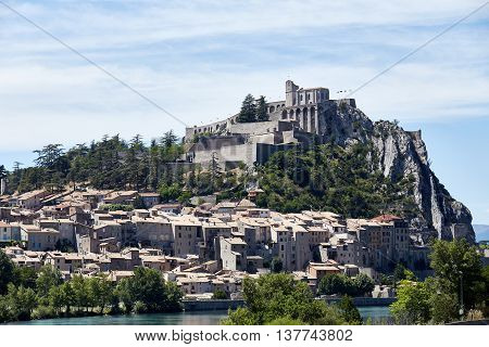 The village is on a hill in the French Alps. Beautiful view of town in mountains in summer. The village is on a hill. Small houses and buildings.