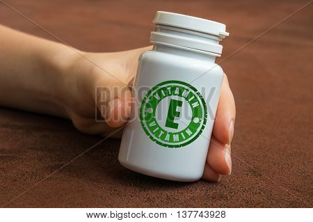 Human Hand Holding A Bottle Of Pills With Vitamin E
