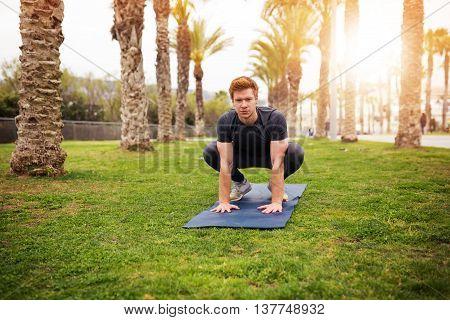 Man Crouching On The Gym Mat