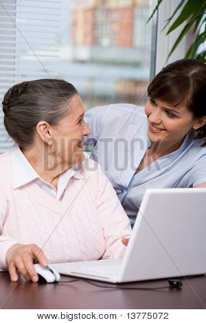 Portrait of young girl speaking to her grandmother while consulting how to work with laptop