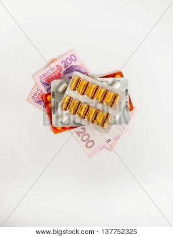 pills on money on a white background concept
