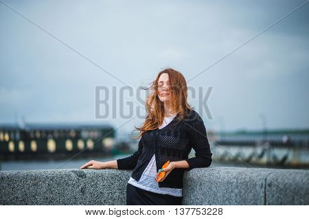 Brown haired girl with closed eyes and flying hair on wind standing at river bank. Concept of a bad, windy weather, loneliness.