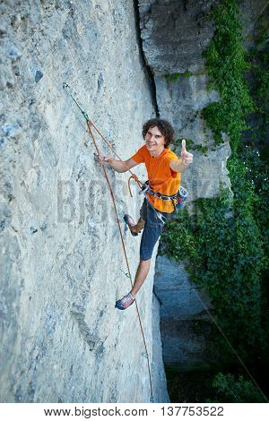 male rock climber. rock climber climbs on a rocky wall. man show ThumbUp gesture, sign.