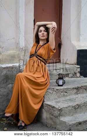 Beautiful boho style girl in a long dress posing in the street