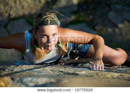 Image of blonde lady climbing on the rock