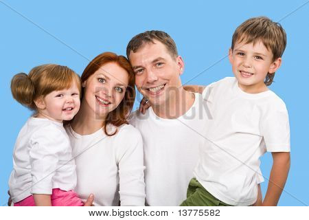 Photo of joyful parents holding children on hands on a sky background