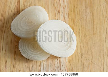 Young sliced onion rings on a wooden board