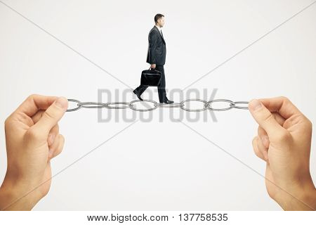 Balancing concept with businessman miniature walking on chain held by hands on white background