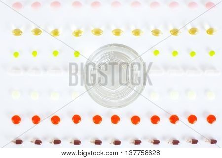 Top view of white surfcace with rows of different pills capsules and a glass of water