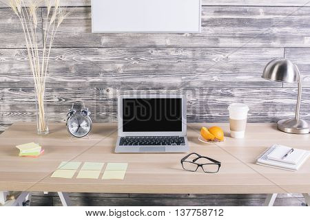 Creative designer desktop with blank laptop screen alarm wheat spikes lamp coffee cup blank picture frames and many other items. Mock up