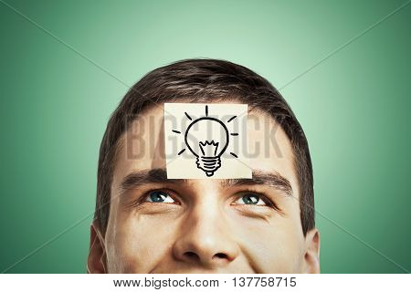 Idea concept with lightbulb sketch drawn on sticker glued to happy guy's forehead on green background