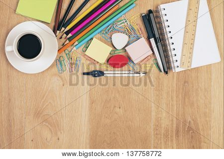 Top view of messy wooden desktop with coffee cup and colorful stationery items. Mock up