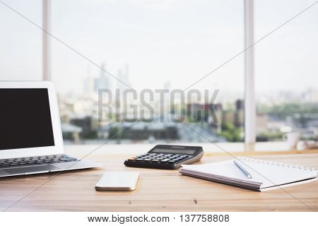 Front view of wooden office desktop with blank notebook calculator smartphone and stationery items on blurry city background. Mock up