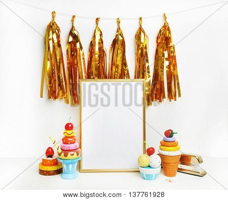 Mockup frame.Gold frame and white wall. Gold tassel and sweet bar. Ice cream cupcakes cherry.