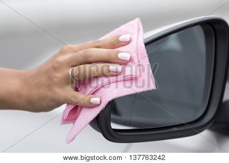 Woman's hand with a cloth to clean the mirror car washes