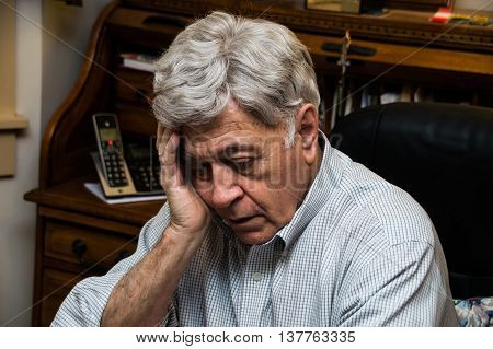 Older man resting his head in his hand and gazing downward with a tired, sad, thoughtful, pensive expression on his face.