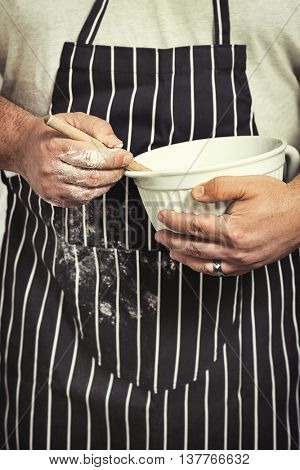 Baker in apron covered with flour holding mixing bowl and wooden spoon