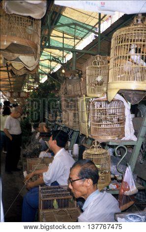 GUANGZHOU / CHINA - CIRCA 1987: Vendors sell pet birds in cages in Guangzhou's Qingping Market.