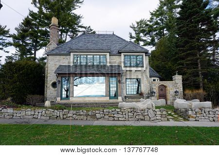HARBOR SPRINGS, MICHIGAN / UNITED STATES - DECEMBER 25, 2015: An elegant stone home on East Bluff Drive in Harbor Springs, Michigan, with a view of Little Traverse Bay.