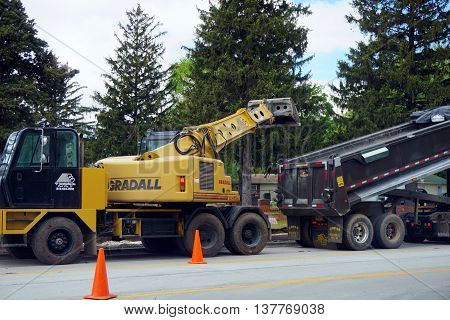 PLAINFIELD, ILLINOIS / UNITED STATES - MAY 4, 2016: A  yellow Gradall XL 4100 IV Hydraulic Excavator places dirt into a dumptruck at a road construction project on Renwick Road in Plainfield.