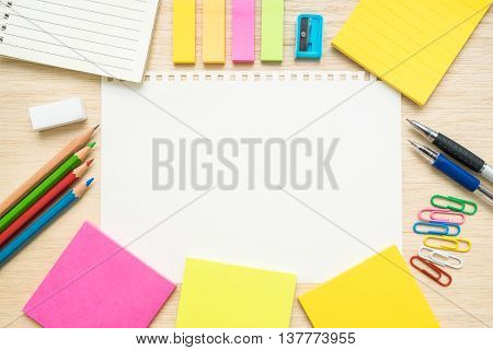 Desk above table top view of stationery items - pen pencil colored pencils paper clips sticky notes sharpener eraser notepad notebook and empty line paper in the center on wooden background