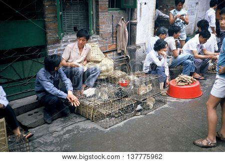 GUANGZHOU / CHINA - CIRCA 1987: Vendors sell rabbits and cats in cages in Guangzhou's Qingping Market.