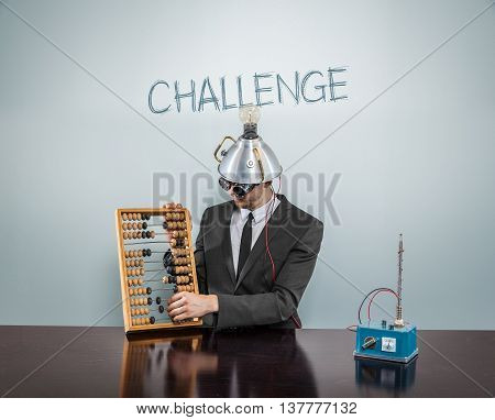 Challenge concept with businessman and abacus at office