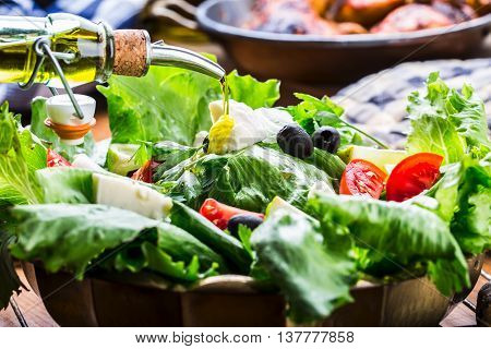 Vegetable lettuce salad. Olive oil pouring into bowl of salad. Italian Mediterranean or Greek cuisine. Vegetarian vegan food.