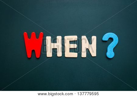 Text 'when' wording on blackboard - business concept of 5 WHs questions - problem solving - colorful alphabet made from wood