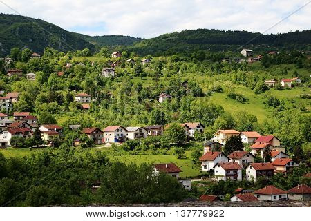 Scenic hill town of Jajce Bosnia and Herzegovina with sunlight piecing through dark clouds and shining on the hill