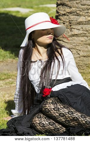 CAGLIARI ITALY - June 1, 2014: Sunday at La Grande Jatte public gardens - Sardinia - portrait of a beautiful girl in Victorian costumes sitting in the shade of a plant