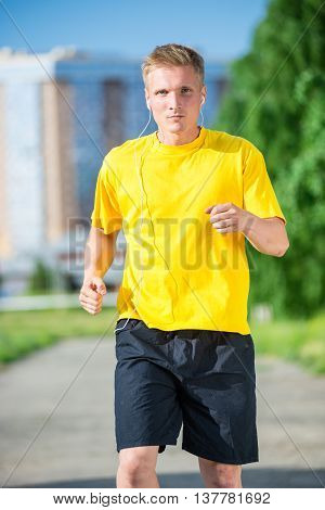 Running man jogging in city street park at beautiful summer day. Sport fitness model caucasian ethnicity training outdoor. Jogger listening training music on smartphone