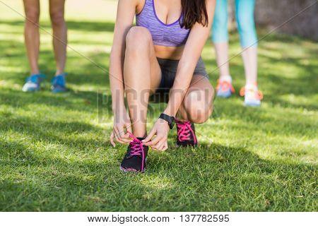 Woman tying shoe lace in park