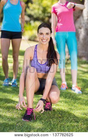 Portrait of woman tying shoe lace in park