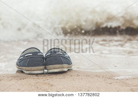 canvas shoes on sand beach with copy space on rightvintage filter