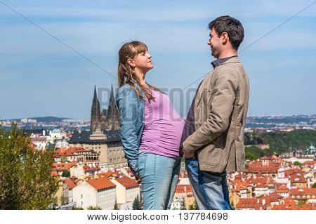 Pregnant young lady and a young man watching each other and compare their bellies in Prague Czech Republic