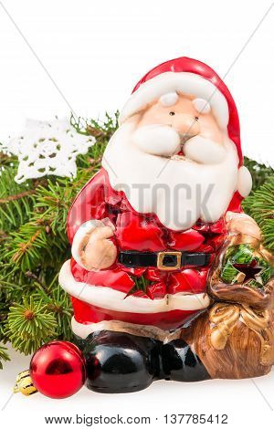 figurine of Santa Claus near the branch of a Christmas tree isolated closeup