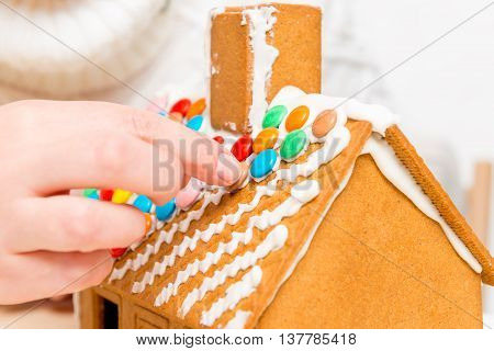Women's Hands Are Fixed To The Roof Of Colored Dragees Of Gingerbread House
