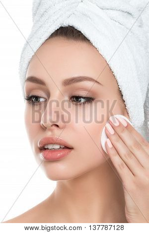 Portrait of young beautiful woman with towel on her hair cleaning makeup from her face with cosmetic pad isolated over white background. Cleaning face perfect skin skincare and cosmetology concept