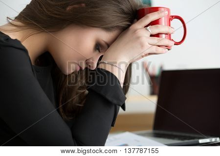 Tired female employee at workplace in office holding red cup and touching her head. Sleepy worker early in the morning. Overworking making mistake stress termination or depression concept