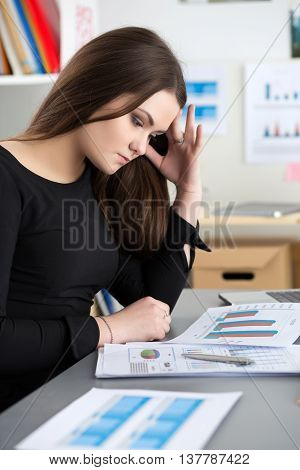 Tired female employee at workplace in office touching her head trying to concentrate. Sleepy worker early in the morning. Overworking making mistake stress termination or depression concept