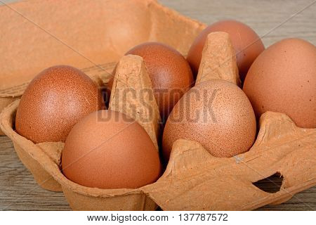 Six fresh brown eggs in a brown cardboard box