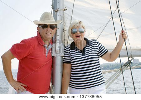 Happy middle aged couple in eyeglasses looking at camera and smiling standing near the mast on the yacht