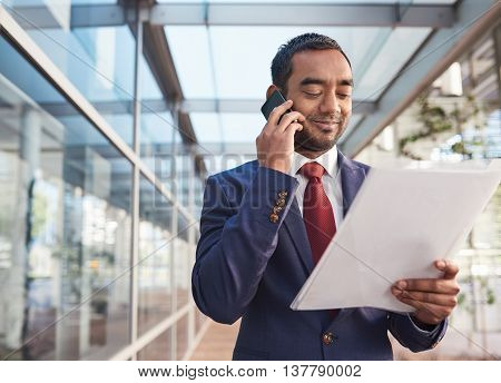 Confident and successful businessman talking on a cellphone and reading paperwork while standing in front of the glass windows of a modern office building