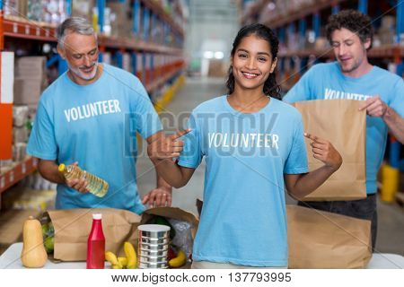 Happy volunteer showing her tee-shirt to the camera in front of her team in a warehouse